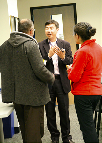 Dr. Wang speaks with colleagues after his talk.